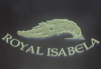 The wind-swept native oak tree logo of Royal Isabela on the bag of Miguel Suarez..