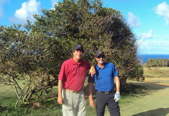 Stanley Pasarell with Miguel Suarez on the 18th fairway in front of the logo wind-swept native oak tree of Royal Isabela.
