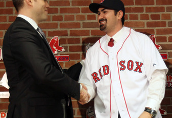 BOSTON, MA - DECEMBER 06:  Adrian Gonzalez (R) shakes hands with Boston Red Sox General Manager Theo Epstein after it was announced that Gonzalez signed with the Boston Red Sox on December 6,  2010 at Fenway Park in Boston, Massachusetts.  (Photo by Elsa/
