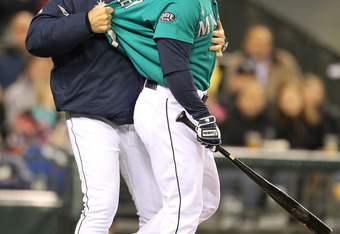 SEATTLE - MAY 06:  Milton Bradley #15 of the Seattle Mariners is restrained by manager Eric Wedge #22 after being ejected from the game against the Chicago White Sox at Safeco Field on May 6, 2011 in Seattle, Washington. (Photo by Otto Greule Jr/Getty Ima
