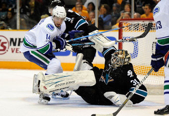 SAN JOSE, CA - MAY 20:  Alex Burrows #14 of the Vancouver Canucks skates in the crease area as goaltender Antti Niemi #31 of the San Jose Sharks falls to the ice in Game Three of the Western Conference Finals during the 2011 Stanley Cup Playoffs at HP Pav