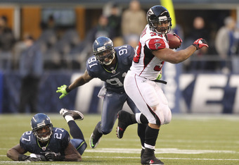 SEATTLE, WA - DECEMBER 19:  Running back Michael Turner #33 of the Atlanta Falcons rushes against Chris Clemons #91 and Jordan Babineaux #27 of the Seattle Seahawks at Qwest Field on December 19, 2010 in Seattle, Washington. The Falcons defeated the Seaha