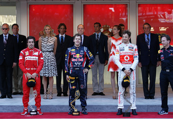 MONTE CARLO, MONACO - MAY 29:  Race winner Sebastian Vettel (C) of Germany and Red Bull Racing celebrates with second placed Fernando Alonso (L) of Spain and Ferrari and third placed Jenson Button (R) of Great Britain and McLaren after the Monaco Formula