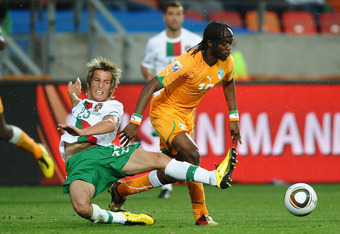 PORT ELIZABETH, SOUTH AFRICA - JUNE 15:  Gervinho of Ivory Coast is tackled by Fabio Coentrao of Portugal during the 2010 FIFA World Cup South Africa Group G match between Ivory Coast and Portugal at Nelson Mandela Bay Stadium on June 15, 2010 in Port Eli