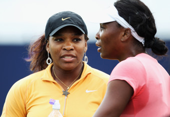EASTBOURNE, ENGLAND - JUNE 11:  Serena Williams (L) of the USA chats to her sister Venus during a break in practice for the AEGON International on June 11, 2011 in Eastbourne, England.  (Photo by Bryn Lennon/Getty Images)
