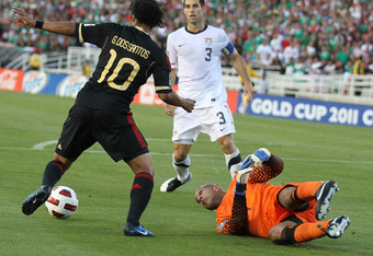 PASADENA, CA - JUNE 25: Giovani Dos Santos #10 of  Mexico gets the ball away from goal keeper Tim Howard #1 of the United States to set up his goal during the 2011 CONCACAF Gold Championship at the Rose Bowl on June 25, 2011 in Pasadena, California. Mexic