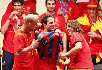MADRID, SPAIN - JULY 12:  Pepe Reina (L) and Carles Puyol (R) of the Spanish national football team put a FC Barcelona shirt on Cesc Fabregas during the Spanish team's parade following their victory in the 2010 FIFA World Cup on July 12, 2010 in Madrid, S