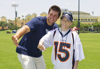 LAKE BUENA VISTA, FL - JUNE 13:  In this handout photo provided by Disney Parks, former University of Florida and current Denver Broncos quarterback Tim Tebow (left) and Adam Hubbs, 16, strike a 'Heisman Trophy' pose June 13, 2011 at ESPN Wide World of Sp