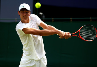 LONDON, ENGLAND - JUNE 27:  Bernard Tomic of Australia returns a shot during his fourth round match against Xavier Malisse of Belgium on Day Seven of the Wimbledon Lawn Tennis Championships at the All England Lawn Tennis and Croquet Club on June 27, 2011