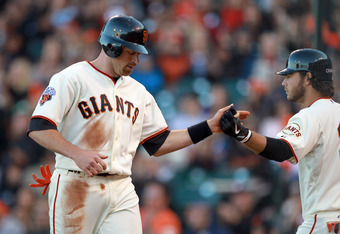 SAN FRANCISCO, CA - JUNE 12:  Nate Schierholtz #12 of the San Francisco Giants is congratulated by Brandon Crawford #35 of the San Francisco Giants after he scored to tie the score 2-2 in the sixth inning against the Cincinnati Reds at AT&T Park on June 1