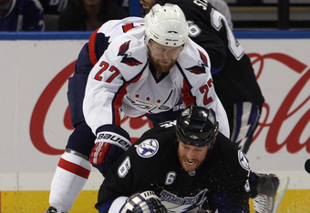 TAMPA, FL - MAY 04: Karl Alzner #27 of the Washington Capitals knocks Ryan Malone #6 of the Tampa Bay Lightning to the ice in the first period in Game Four of the Eastern Conference Semifinals during the 2011 NHL Stanley Cup Playoffs at the St Pete Times