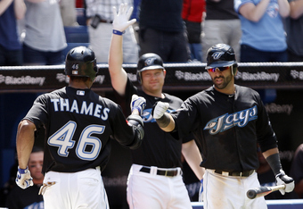 Eric Thames gets congratulations from teammates Jose Bautista and Adam Lind after hitting his third home run.