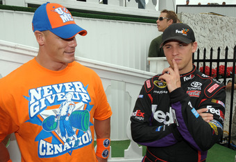 LONG POND, PA - JUNE 06:  WWE champion and co-grand marshal John Cena (L) and Denny Hamlin, driver of the #11 FedEx Freight Toyota, talk in Victory Lane prior to the NASCAR Sprint Cup Series Gillette Fusion ProGlide 500 at Pocono Raceway on June 6, 2010 i