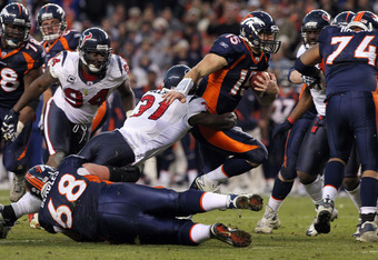 DENVER - DECEMBER 26:  Quarterback Tim Tebow #15 of the Denver Broncos rushes with the ball and is tackled by strong safety Bernard Pollard #31 of the Houston Texas at INVESCO Field at Mile High on December 26, 2010 in Denver, Colorado. The Broncos defeat