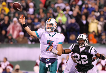 EAST RUTHERFORD, NJ - DECEMBER 12:  Chad Henne #7 of the Miami Dolphins passes under pressure from Brodney Pool #22 of the New York Jets at New Meadowlands Stadium on December 12, 2010 in East Rutherford, New Jersey.  (Photo by Nick Laham/Getty Images)