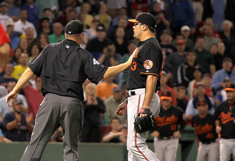 BOSTON, MA - JULY 8:  Kevin Gregg #63 of the Baltimore Orioles is held back by an umpire after he and David Ortiz exchanged words in the eighth inning at Fenway Park on July 8, 2011 in Boston, Massachusetts.  Later that inning Ortiz and Gregg would exchan