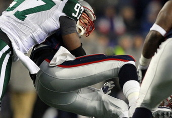 FOXBORO, MA - JANUARY 16:  Tom Brady #12 of the New England Patriots looses the ball as he is sacked by Calvin Pace #97 of the New York Jets in the third quarter of their 2011 AFC divisional playoff game at Gillette Stadium on January 16, 2011 in Foxboro,