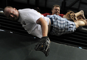 This idiot was spared by the quick thinking of his friends at the home run derby. He thought it wise to stand on a table near the railing to catch home runs. He was wrong.
