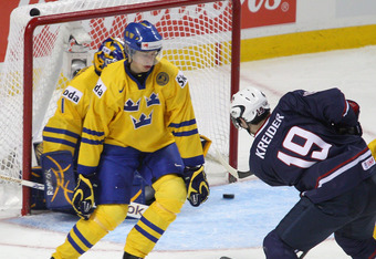 BUFFALO, NY - JANUARY 05: Chris Kreider #19 of the United States slides the puck past Adam Larsson #5 and Fredrik Petersson Wentzel #1 of Sweden for the United States first goal during the 2011 IIHF World U20 Championship Bronze medal game between United