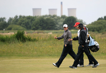 SANDWICH, ENGLAND - JULY 14:  Rory McIlroy of Northern Ireland walks with caddy JP Fitzgerald and Rickie Fowler of the United States during the first round of The 140th Open Championship at Royal St George's on July 14, 2011 in Sandwich, England.  (Photo