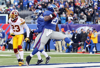 EAST RUTHERFORD, NJ - DECEMBER 05:  Brandon Jacobs #27 of the New York Giants carries the ball past DeAngelo Hall #23 of the Washington Redskins for a first quarter touchdown on December 5, 2010 at the New Meadowlands Stadium in East Rutherford, New Jerse