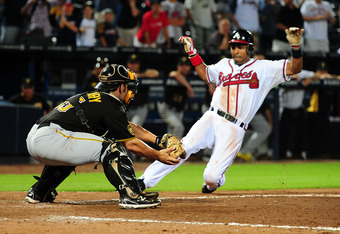 ATLANTA - JULY 26: Julio Lugo #28 of the Atlanta Braves scores the game-winning run in the 19th inning against Michael McKenry #55 of the Pittsburgh Pirates at Turner Field on July 26, 2011 in Atlanta, Georgia. (Photo by Scott Cunningham/Getty Images)