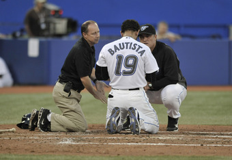 TORONTO, CANADA - JULY 26:  Jose Bautista #19 of the Toronto Blue Jays gets checked out by Assistant Trainer Hap Hudson and General Manager John Farrell after Bautista was hit in the head by a pitch during MLB game action against the Baltimore Orioles Jul
