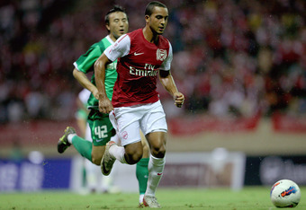 HANGZHOU, CHINA - JULY 16:  Theo Walcott (R) of Arsenal battles for the ball during the pre-season friendly match between Hangzhou Greentown and Arsenal at Yiwu Meihu Stadium on July 16, 2011 in Hangzhou, China.  (Photo by Lintao Zhang/Getty Images)