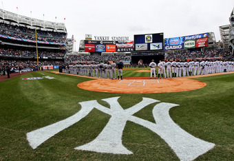 NEW YORK, NY - MARCH 31:  The New York Yankees and the Detroit Tigers look on as West Point Cadets unfurl the American Flag during the opening ceremonies on Opening Day at Yankee Stadium on March 31, 2011 in Bronx borough of New York City.  (Photo by Nick