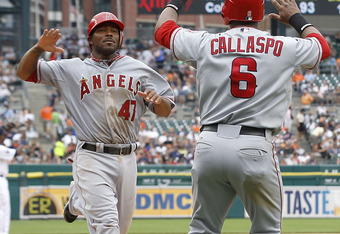 DETROIT - JULY 28: Howie Kendrick #47 of the Los Angeles Angeles of Anaheim scores on a Mark Trumbo #44 triple and is congratulated by teammate Alberto Callaspo #6 during the fourth inning of the game against the Detroit Tigers at Comerica Park on July 28