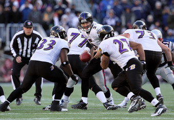 FOXBORO, MA - JANUARY 10: Quarterback Joe Flacco #5  of the Baltimore Ravens turns to hand the ball off against the New England Patriots during the 2010 AFC wild-card playoff game at Gillette Stadium on January 10, 2010 in Foxboro, Massachusetts.  (Photo