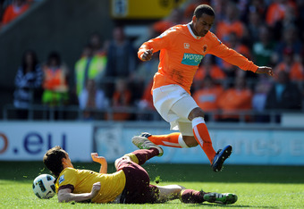 BLACKPOOL, ENGLAND - APRIL 10:  Sebastien Squillaci of Arsenal challenges DJ Campbell of Blackpool during the Barclays Premier League match between Blackpool and Arsenal at Bloomfield Road on April 10, 2011 in Blackpool, England.  (Photo by Chris Brunskil