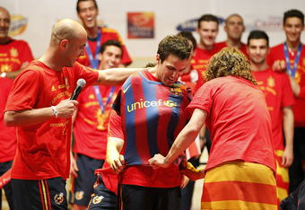 MADRID, SPAIN - JULY 12:  Pepe Reina and Carles Puyol of Spanish national football team put on a shirt of FC Barcelona to Cesc Fabregas during the Spanish team's victory parade following their victory over the Netherlands in the 2010 FIFA World Cup on Jul