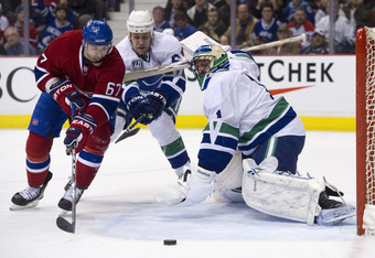 VANCOUVER, CANADA - FEBRUARY 22: Max Pacioretty #67 of the Montreal Canadiens reaches for the loose puck while goalie Roberto Luongo #1 of the Vancouver Canucks scrambles to get back into position while Sami Salo #6 tries to help defend on the play during