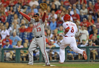 PHILADELPHIA, PA - AUGUST 12: Alex Cora #13 of the Washington Nationals signals not to make the throw as Shane Victorino reaches first on a single at Citizens Bank Park on August 12, 2011 in Philadelphia, Pennsylvania. The Nationals won 4-2. (Photo by Dre