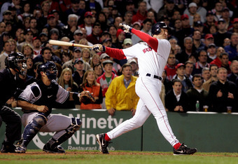 BOSTON - SEPTEMBER 30:  John Olerud #19 of the Boston Red Sox hits a sacrifice fly ball to score Manny Ramirez #24 in the sixth inning making it 5-1 against the New York Yankees during the game at Fenway Park on September 30, 2005 in Boston, Massachusetts