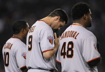 LOS ANGELES, CA - APRIL 01:  Brandon Belt (second from left) #9 of the San Francisco Giants lowers his head during the signing of  'God Bless America' in the seventh inning against the Los Angeles Dodgers at Dodger Stadium on April 1, 2011 in Los Angeles,