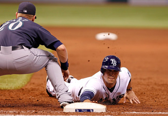 ST. PETERSBURG, FL - AUGUST 19:  Outfielder Sam Fuld #5 of the Tampa Bay Rays dives back safely to first as first baseman Mike Carp #20 of the Seattle Mariners is late with the tag during the game at Tropicana Field on August 19, 2011 in St. Petersburg, Florida.  (Photo by J. Meric/Getty Images)