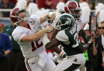 ORLANDO, FL - JANUARY 01:  Greg McElroy #12 of the Alabama Crimson Tide blocks Trenton Robinson #39 of  the Michigan State Spartans on a touchdown run during the Capitol One Bowl at the Florida Citrus Bowl on January 1, 2011 in Orlando, Florida.  (Photo by Mike Ehrmann/Getty Images)