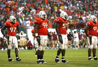 MIAMI - OCTOBER 04:  Defenders Adewale Ojomo #97, Antonio Dixon #96, Allen Bailey #57 and Marcus Forston #99 of the Miami Hurricanes wait for the next play while taking on the Florida State Seminoles at Dolphin Stadium on October 4, 2008 in Miami, Florida. Florida State defeated Miami 41-39.  (Photo by Doug Benc/Getty Images)
