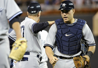 MINNEAPOLIS, MN - AUGUST 19: First base coach Mick Kelleher #50 and Russell Martin #55 of the New York Yankees celebrate a win against the Minnesota Twins on August 19, 2011 at Target Field in Minneapolis, Minnesota. The Yankees defeated the Twins 8-1. (Photo by Hannah Foslien/Getty Images)