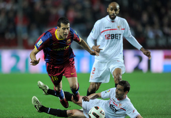 SEVILLE, SPAIN - MARCH 13:  Fernando Navarro (R) of Sevilla fouls Sergio Busquets of Barcelona during the la Liga match between Sevilla and Barcelona at Estadio Ramon Sanchez Pizjuan on March 13, 2011 in Seville, Spain.  (Photo by Jasper Juinen/Getty Images)