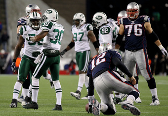 FOXBORO, MA - JANUARY 16:  Tom Brady #12 of the New England Patriots gets up after being sacked by Drew Coleman #30 of the New York Jets during their 2011 AFC divisional playoff game at Gillette Stadium on January 16, 2011 in Foxboro, Massachusetts.  (Photo by Al Bello/Getty Images)