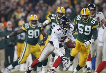 GREEN BAY, WI - JANUARY 4:  Michael Vick #7 of the Atlanta Falcons runs with the ball as he weaves his way through the Green Bay Packer defense during the NFC Wildcard game on January 4, 2002 at Lambeau Field in Green Bay, Wisconsin.  (Photo by Jonathan D