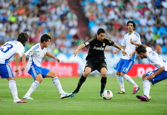 ZARAGOZA, SPAIN - AUGUST 28: Angel di Maria of Real Madrid takes on Franco Zuculini (R) of Real Zaragoza during the La Liga match between Real Zaragoza and Real Madrid at estadio La Romareda on August 28, 2011 in Zaragoza, Spain.  (Photo by Denis Doyle/Ge
