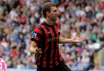 BOLTON, ENGLAND - AUGUST 21:  Edin Dzeko of Manchester City celebrates scoring his team's third goal during the Barclays Premier League match between Bolton Wanderers and Manchester City at the Reebok Stadium on August 21, 2011 in Bolton, England.  (Photo