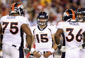 GLENDALE, AZ - SEPTEMBER 01:  Quarterback Tim Tebow #15 (C) of the Denver Broncos stands in the huddle with teammats Chris Clark #75 (L) and Brandon Minor #39 (R) during the preseason NFL game against the Arizona Cardinals at the University of Phoenix Sta