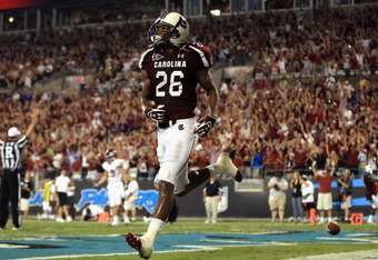 CHARLOTTE, NC - SEPTEMBER 03:  Antonio Allen #26 of the South Carolina Gamecocks celebrates after a touchdown against the East Carolina Pirates during their game at Bank of America Stadium on September 3, 2011 in Charlotte, North Carolina.  (Photo by Stre