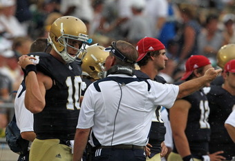 SOUTH BEND, IN - SEPTEMBER 03:  Head coach Brian Kelly of the Notre Dame Fighting Irish talks with Dayne Crist #10 during a game against the University of South Florida Bulls at Notre Dame Stadium on September 3, 2011 in South Bend, Indiana.  (Photo by Jo