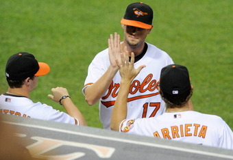 BALTIMORE, MD - JUNE 06:  Brian Matusz #17 of the Baltimore Orioles is congratulated by Zach Britton #53 and Jake Arrieta #34 after leaving the game in the sixth inning against the Oakland Athletics at Oriole Park at Camden Yards on June 6, 2011 in Baltim
